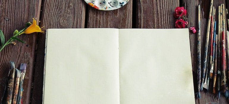 Open notebook with paints around it.