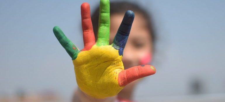 A kid showing colored fingers.
