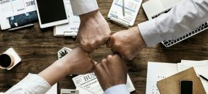 A group of people fist bumping.