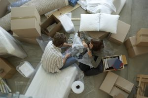 Couple surrounded by boxes packing, representing how to pack for an internation move in a week