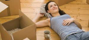 a woman laying on the floor surrounded by moving boxes