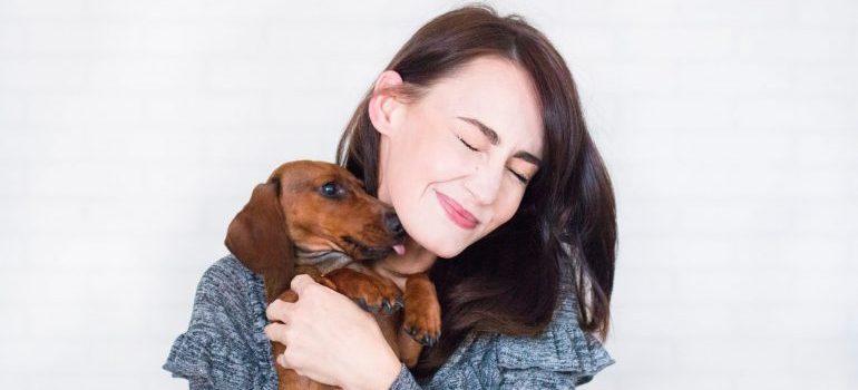 woman-in-grey-top-hugging-brown-dachshund