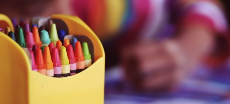 Kid drawing with crayons