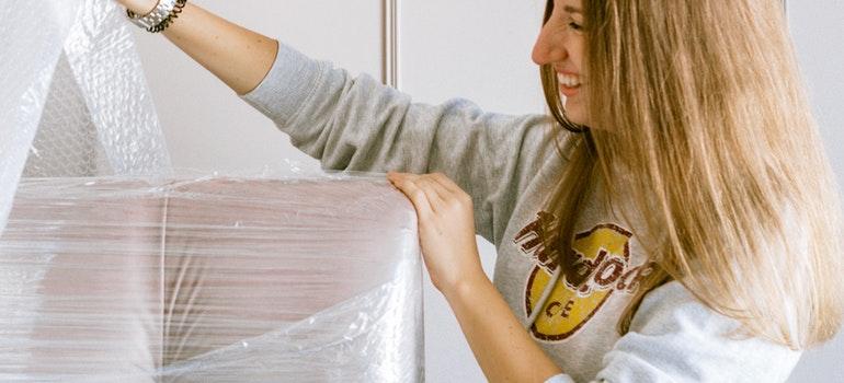 Woman bubble wrapping a sofa