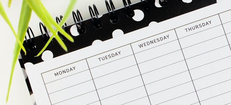 Calendar on a table next to a laptop