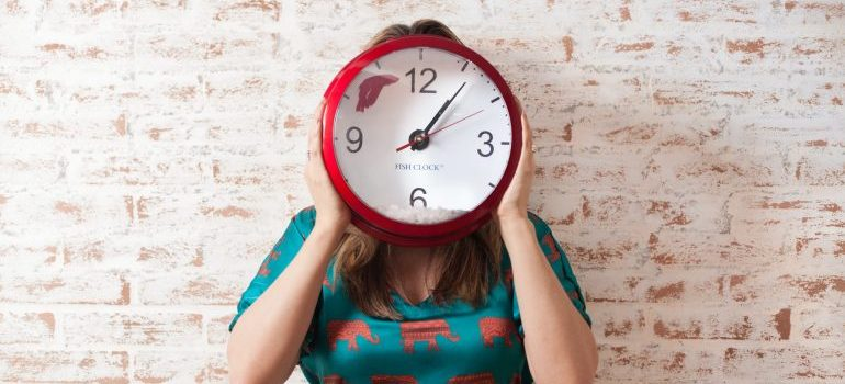 Woman holding a clock in her hands in front of her face