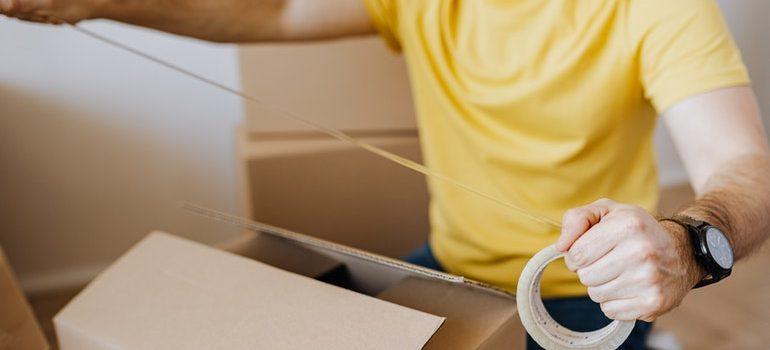 Man taping a box sealed.