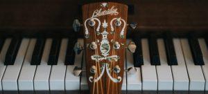 A guitar handle leaned on piano keys