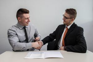 Two men shaking hands after making a deal