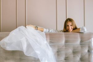 A woman smiling behind the wrapped couch