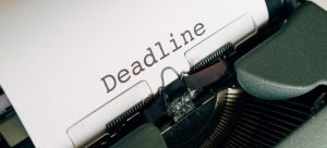 A typewriter with paper coming from it with the word Deadline on it