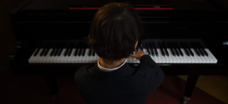 child playing a piano in a music schools
