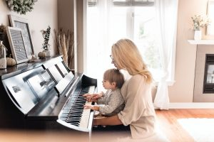 mother playing piano with her baby