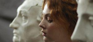 -woman sitting between sculptures