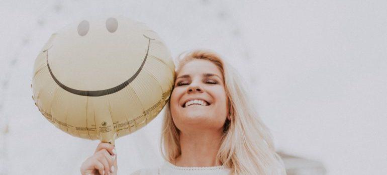 A woman holding a smiley balloon