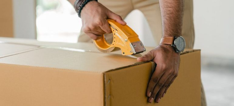 a man taping the box - negotiate with movers
