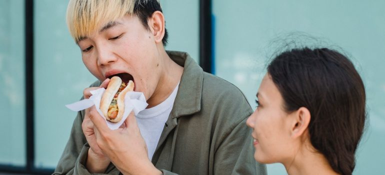 Man eating a hot dog while walking with his girlfriend