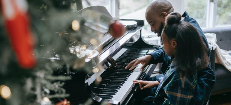 Father playing the piano with her daughter