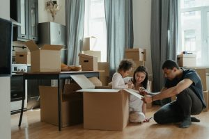 A couple packing their moving boxes and trying to have a fun move with their kids