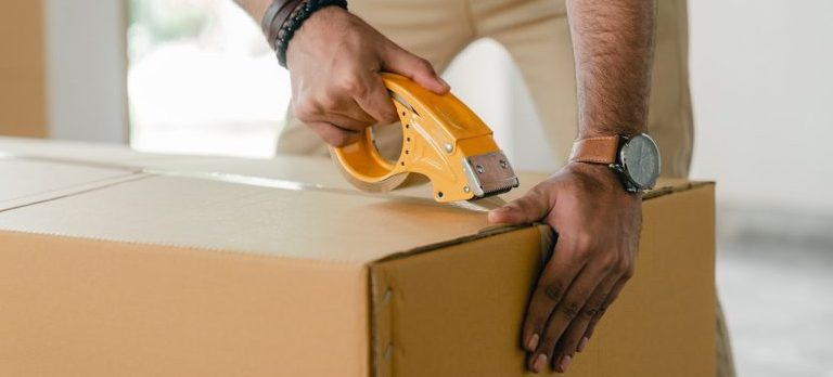 A man from packing services NYC sealing a moving box.