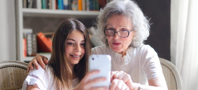 grandmother and granddaughter looking at the cellphone