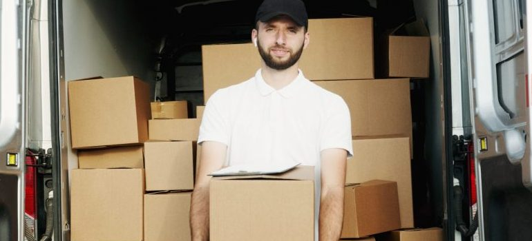 person holding a moving box, a moving van behind
