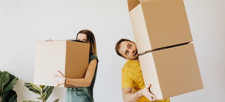 man and woman holding boxes