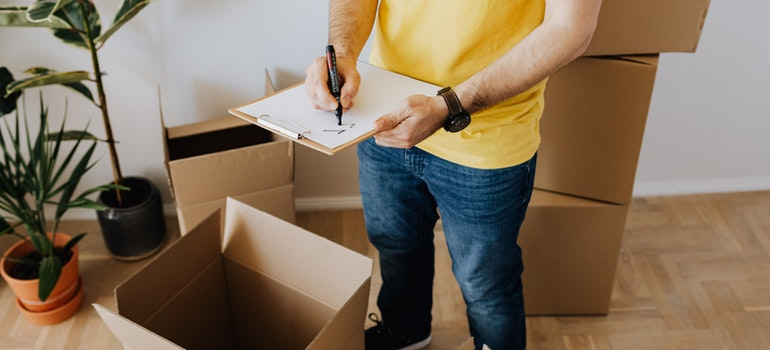 Man taking notes next to boxes