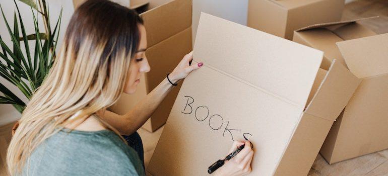 woman writing a on a box