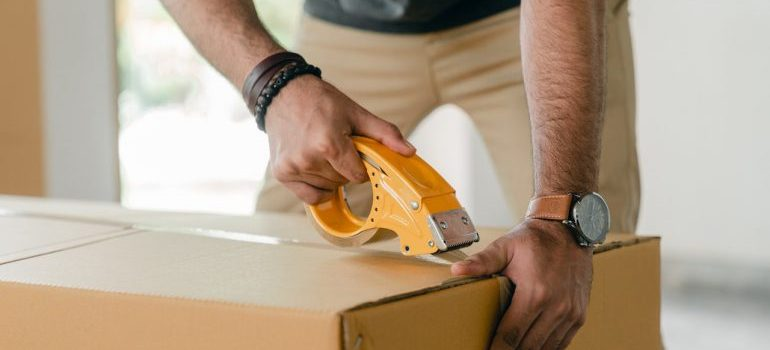 a man sealing a box with a professional tape