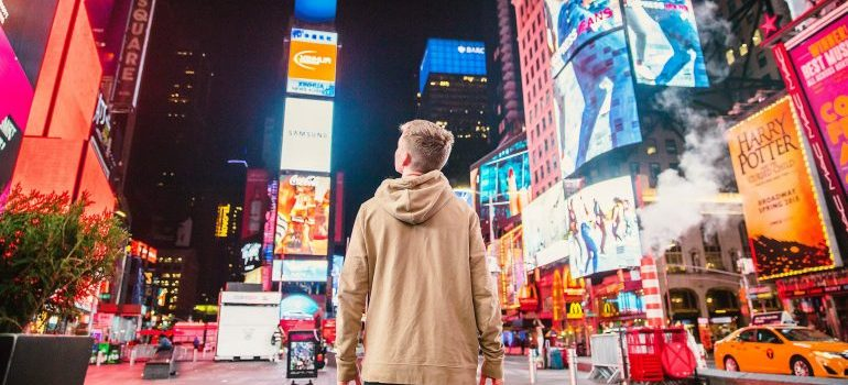 Young guy standing in Times Square at night