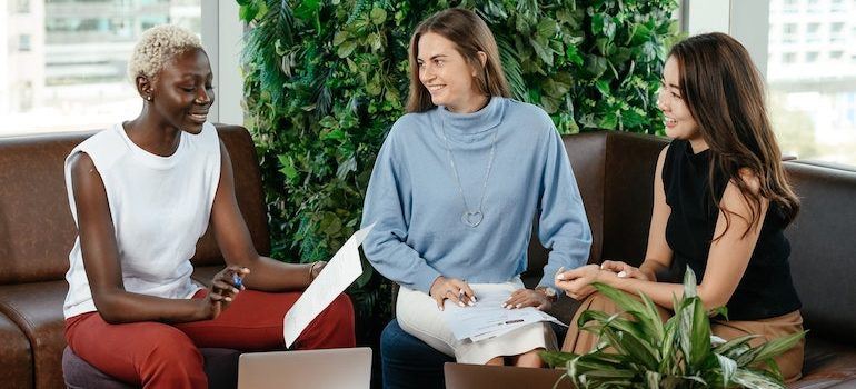 three women talking and holding papers