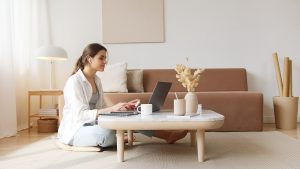 A woman at a table wit a laptop - How to mentally prepare for a move