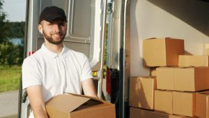 looking at the man holding a box in front of the truck full of boxes helps you answer the question - when should you book your movers