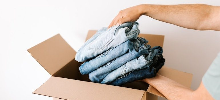 person putting clothing into a box