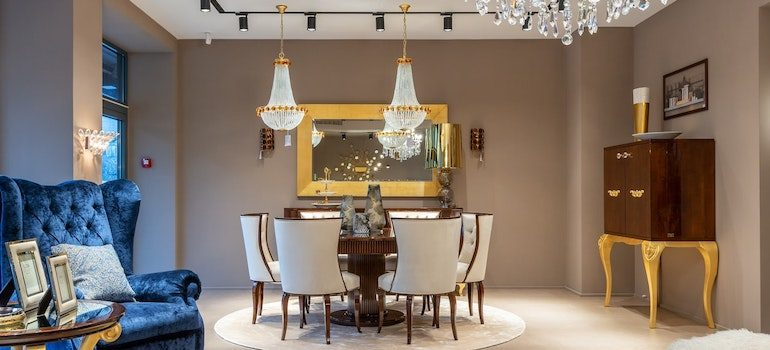 a pair of chandeliers over table and chairs