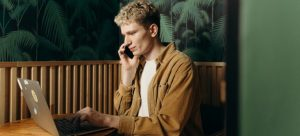 man talking on the phone while tyoing something on the laptop