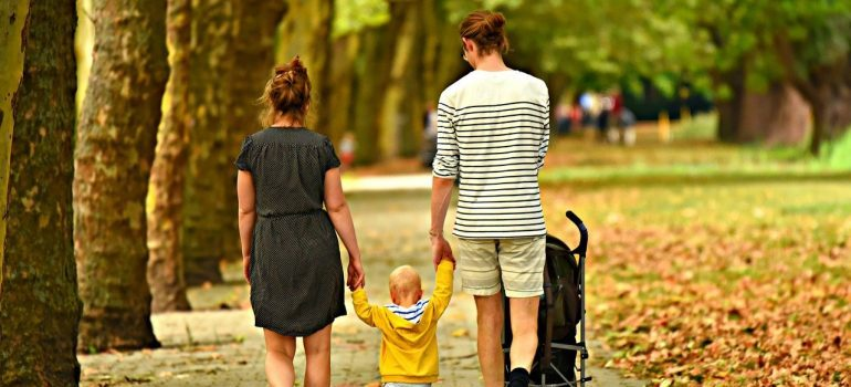 Two parents and a kid walking in the park