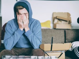 a man holding his head - deal with moving stress