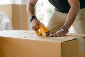 A man packing a cardboard box.