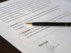 A signed contract with a pen on it