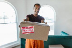 A guy holding a cardboard box