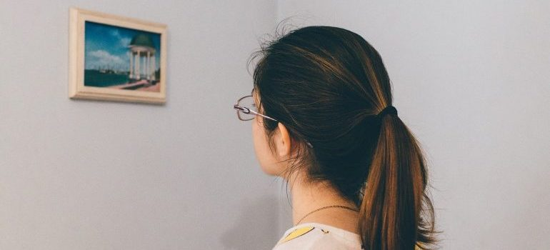 Picture of a woman looking at a painting on the wall