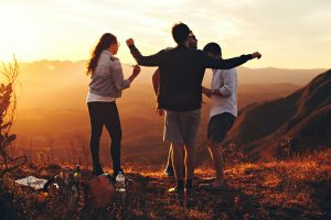Four people standing at the top of a grassy mountain having fun