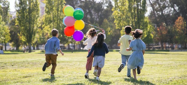 Children playing with baloons on a green grass field