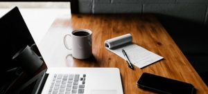 a laptop, a cup, a notebook