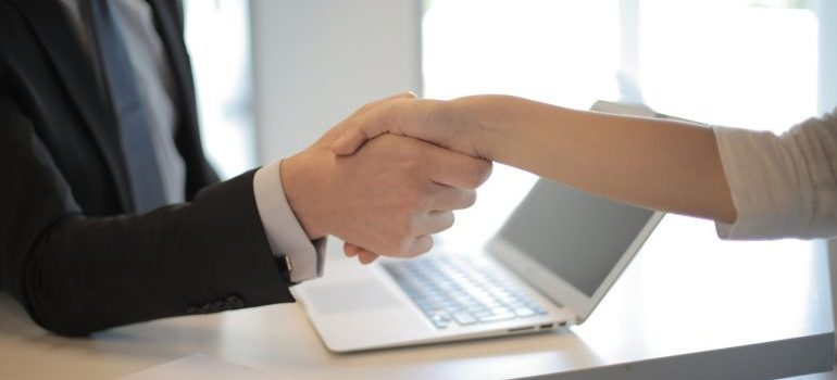 Person shaking hands after hiring movers before moving their piano across Manhattan