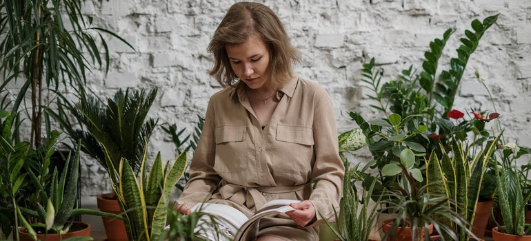 A woman is reading a book while surrounded by plants.