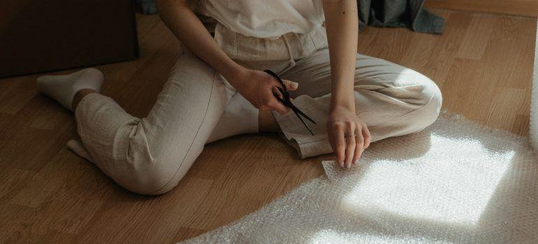 Woman in white pants cutting bubble wrap