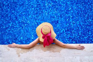 High angle photo of a woman wearing sun hat in a pool